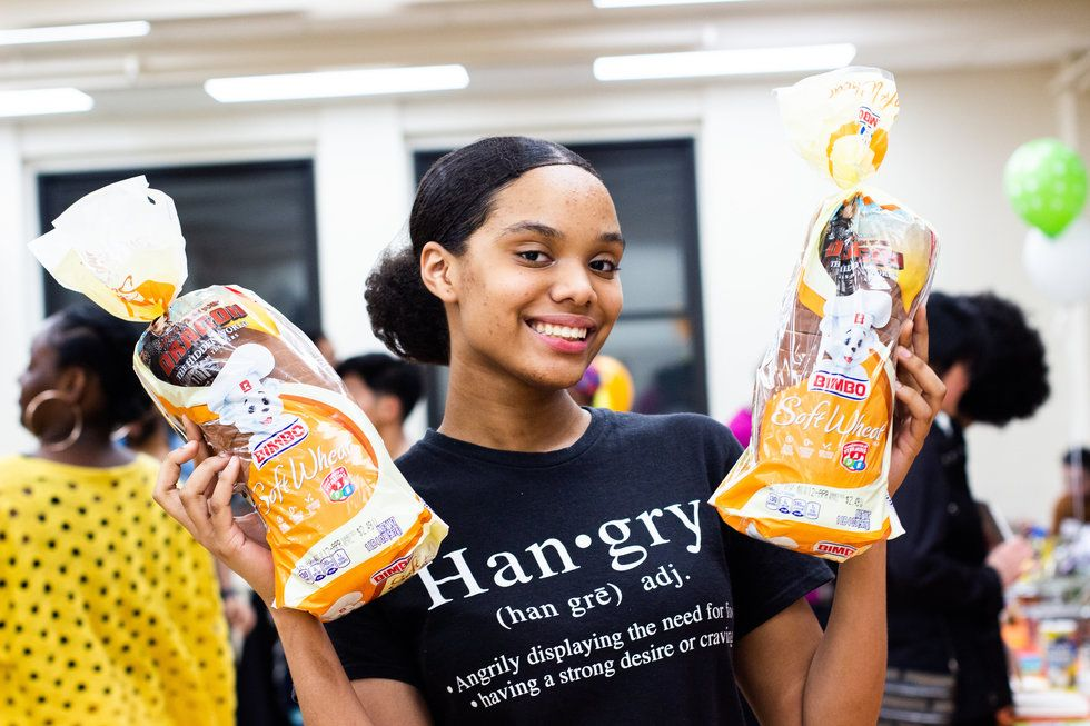 """A young woman smiles and holds up two loaves of bread. Her shirt says """"hangry"""""""