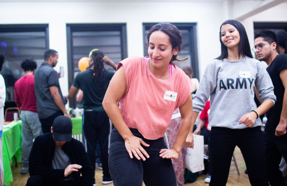 A group dances in the DanceMart while people in the background chat and get food