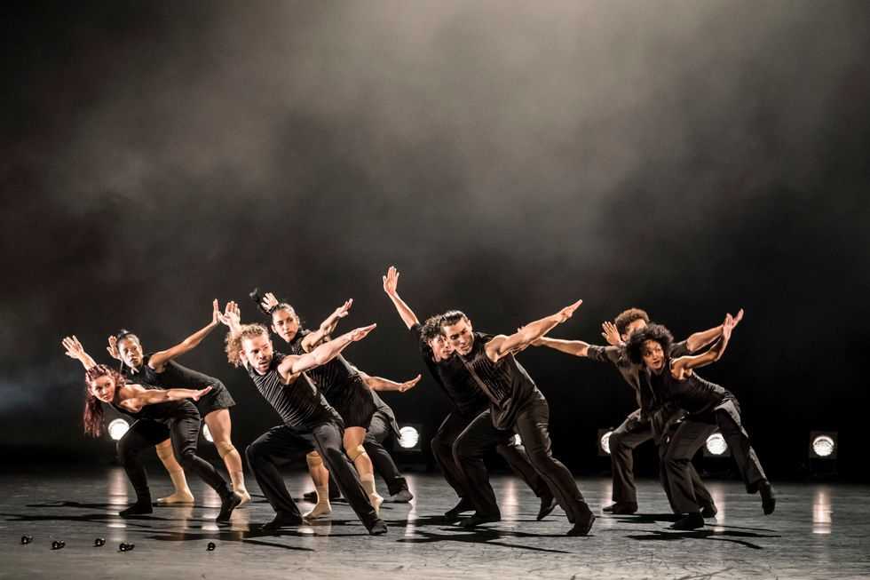Nine male and female dancers, all dressed in black, move through a deep second pli\u00e9, arms flung wide.