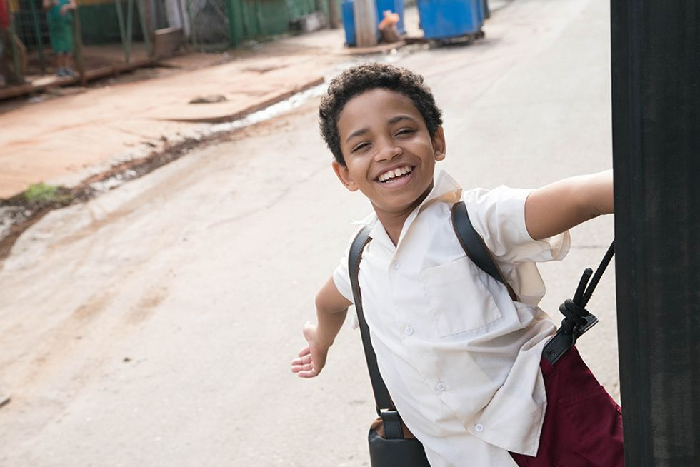 Edlison Manuel Olbera N\u00fa\u00f1ez, playing a young Carlos Acosta in Yuli, grins as he hitches a ride on the side of a moving bus.