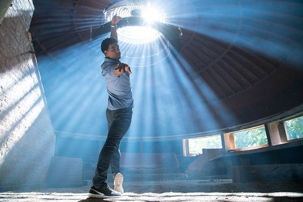 In a still from Yuli, Carlos Acosta, wearing jeans and a button down, looks over his shoulder to the camera from a forced-arch lunge. Sunlight drenches the abandoned building from a circular skylight.
