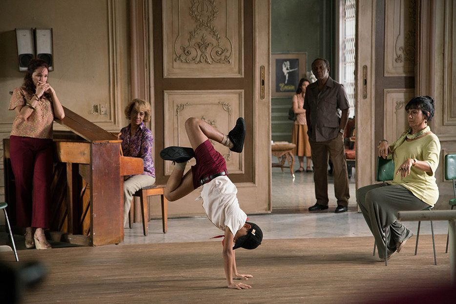Edlison Manuel Olbera N\u00fa\u00f1ez, portraying a young Carlos Acosta in Yuli, does a handstand in sneakers and a baseball cap in the middle of an ornate studio. Two ballet teachers, an older pianist and his father look on with bemusement.