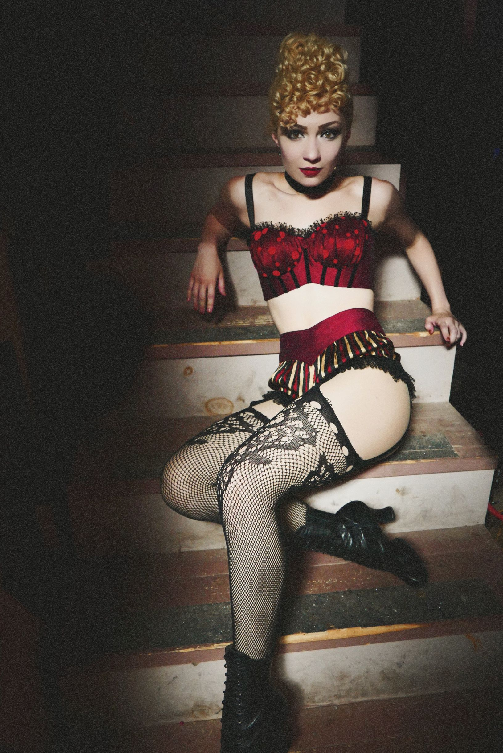 Paloma Garcia-Lee is seated on a staircase. She is wearing a red bra and shorts, black fishnet stockings and black boots.