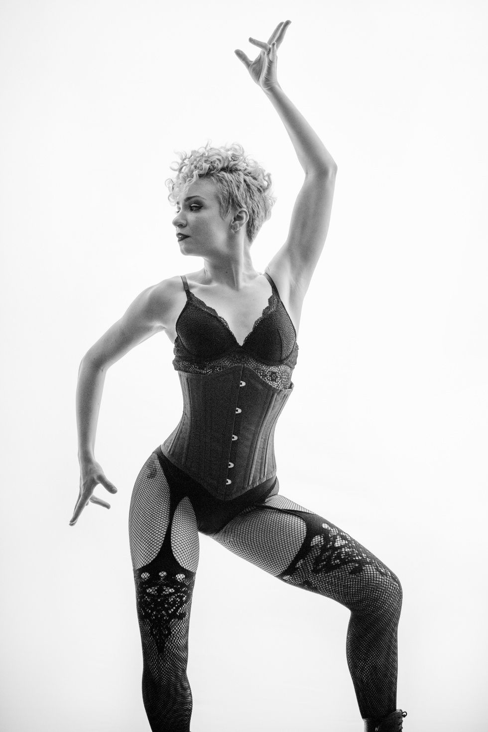 A black-and-white photo of Paloma Garcia-Lee posing in fishnets, lingerie and a corset. One arm is energetically held above her head.