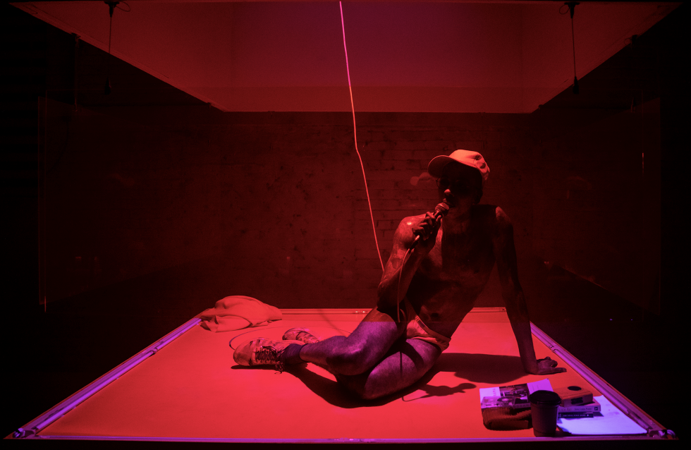 Raja Feather Kelly sits on a stage coated in red light, with a baseball cap and a microphone