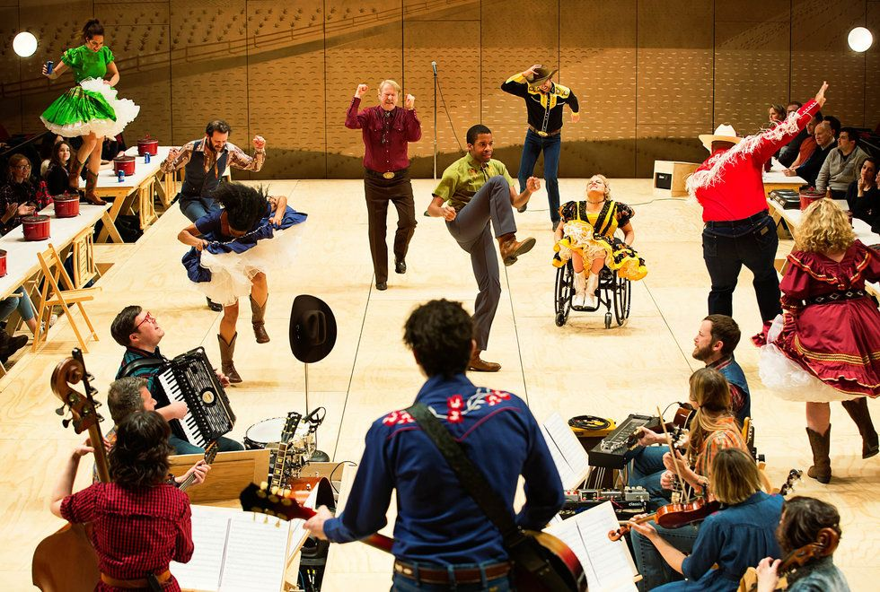 The cast of Oklahoma! in a dance scene, onstage with the show's band.