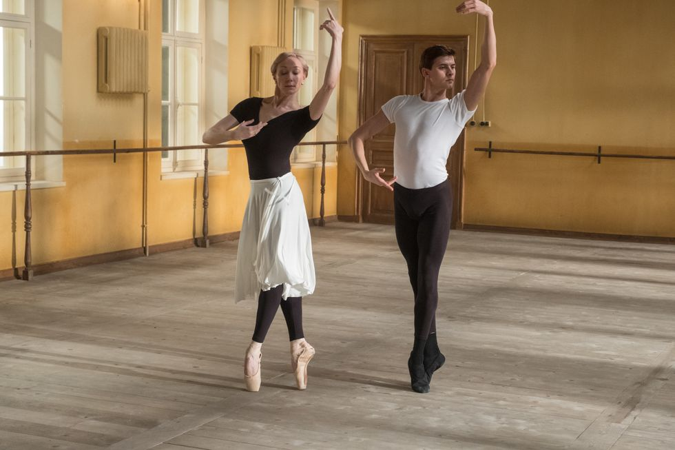 In the White Crow, Natalia Dudinskaya, an older, blonde ballerina, and Rudolf Nureyev rehearse in the studio. Both wear practice clothes and are posed in releve, arms in fourth position.