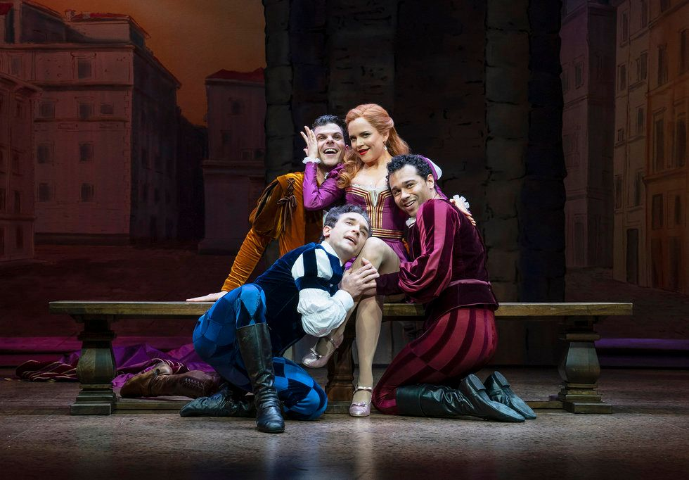 Three men and a woman, all in Shakespearean clothes, pose on a bench. The men are doting on the woman.