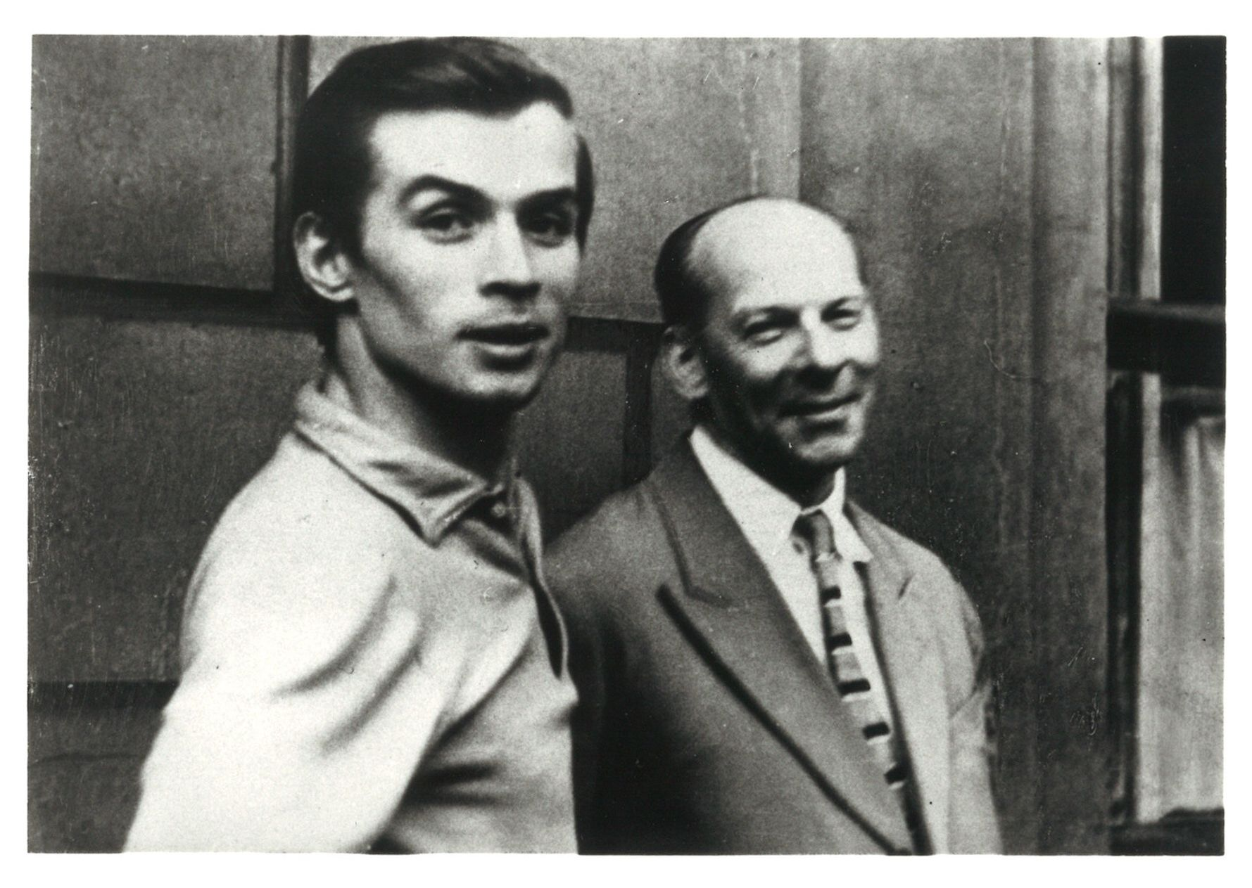 A black and white photograph of a young Rudolf Nureyev and his teacher, Alexander Pushkin, here smiling and wearing a suit and tie.