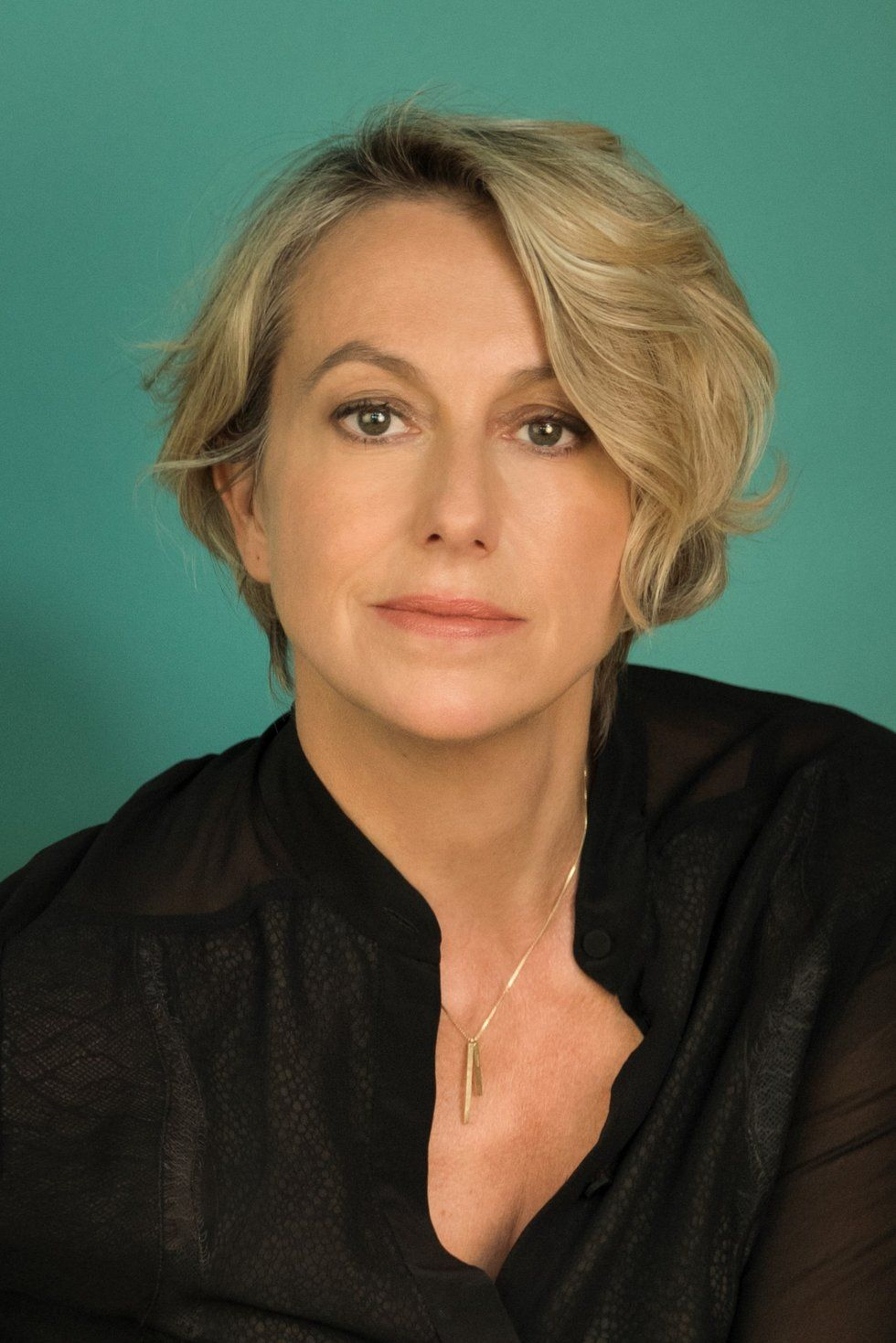 A headshot of page. She has short blond hair and a black shirt and is in front of a teal background.