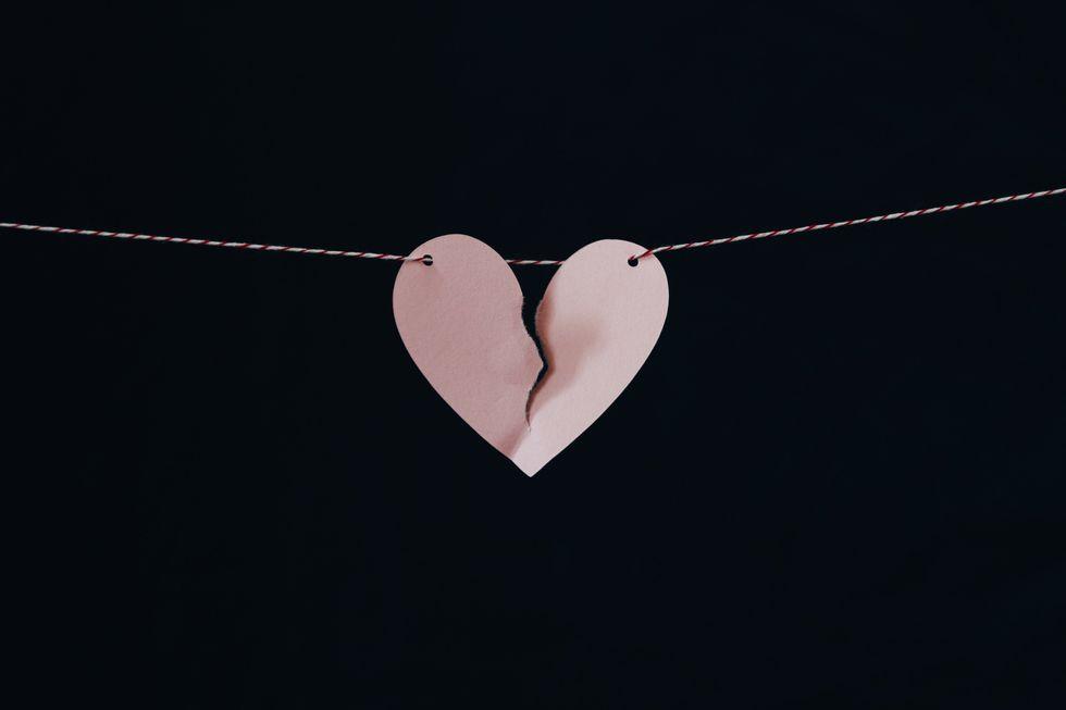 broken paper heart held up on a string