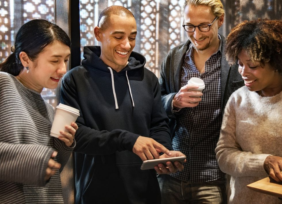 https://www.pexels.com/photo/group-of-men-and-women-smiling-while-looking-at-phone-1289898/