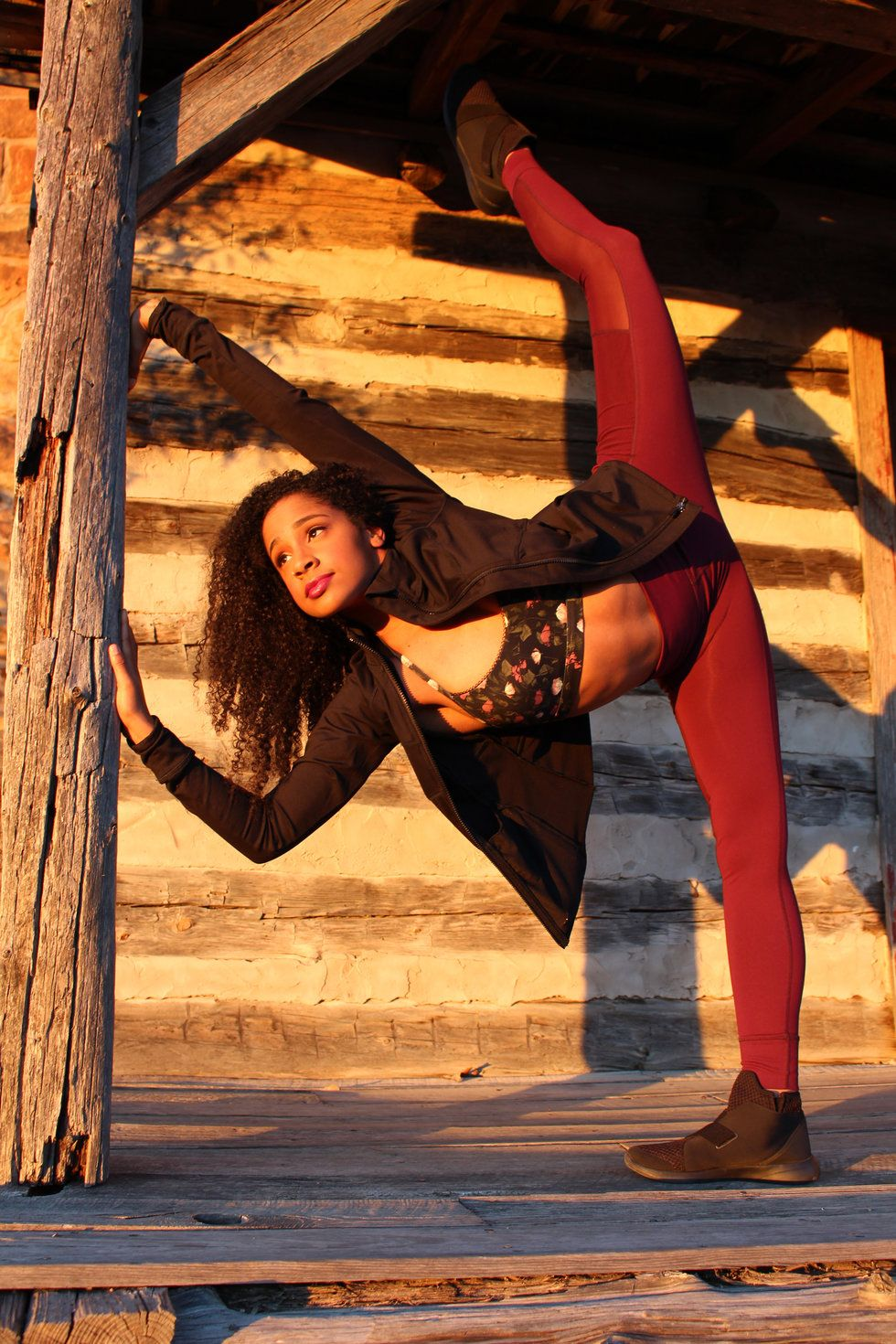 Moore in a pench\u00e9, leaning against a support beam of a rustic, wooden building. She is wearing maroon leggings, a floral crop top and a black jacket.