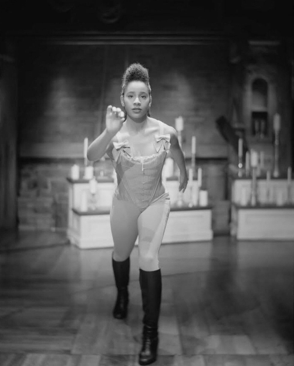 A black-and-white photo of Moore, in costume for Hamilton. She is lunging toward the camera.