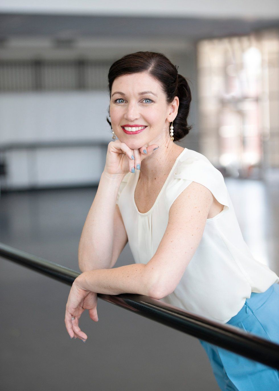 Kathleen Breen Combes leans over a ballet barre