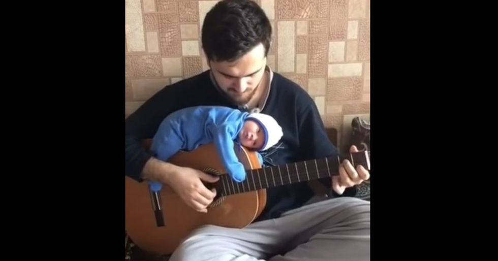 This chill dad serenading his baby to sleep while it rests on top of his guitar is 2019's must-see concert.