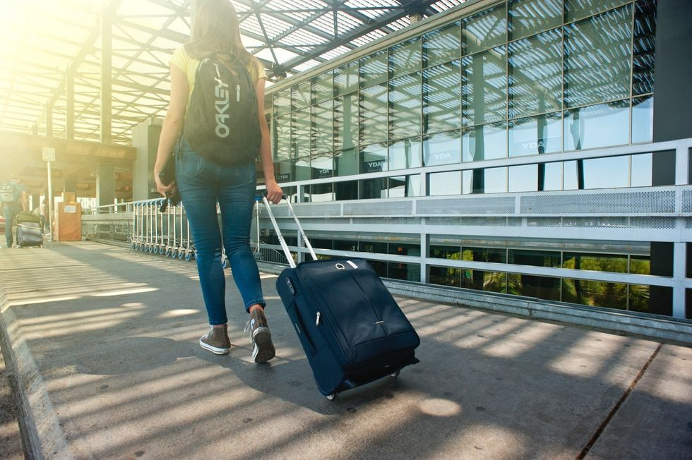 https://www.pexels.com/photo/woman-walking-on-pathway-while-strolling-luggage-1008155/