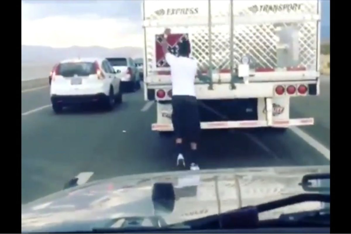 Watch a man peel a confederate flag off of a moving truck in traffic.