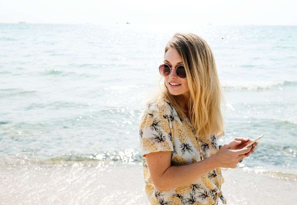 Women on beach in sunglasses posing candidly while on her cell phone