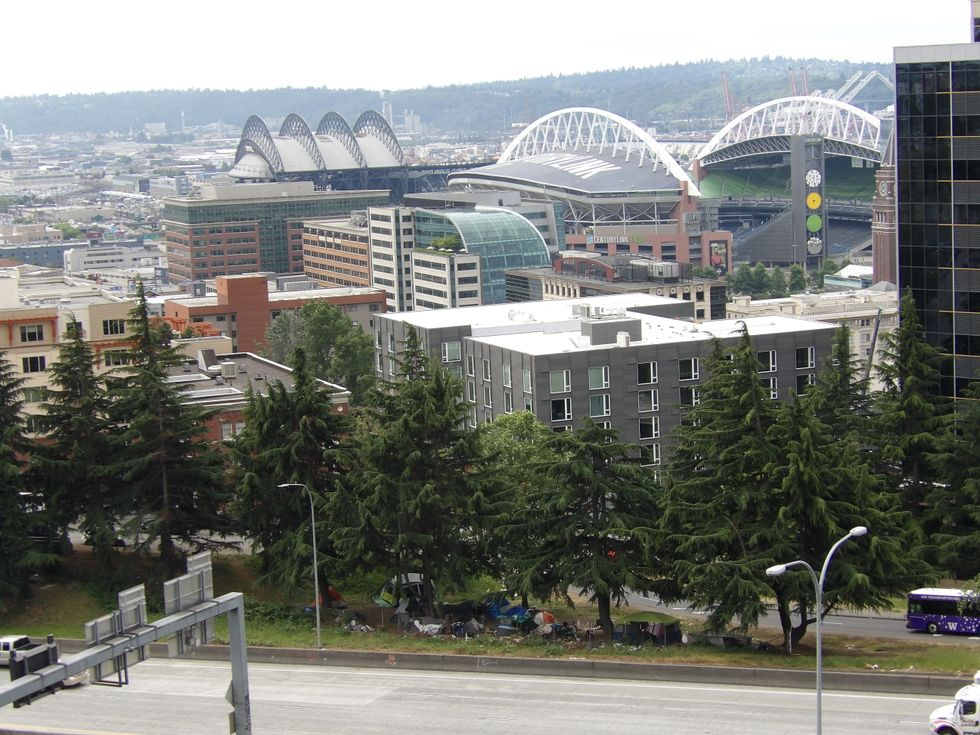 Seattle between CenturyLink Stadium and Interstate 5, including a strip of greenscaped land with large evergreen trees next to the interstate with tents and clutter under the trees