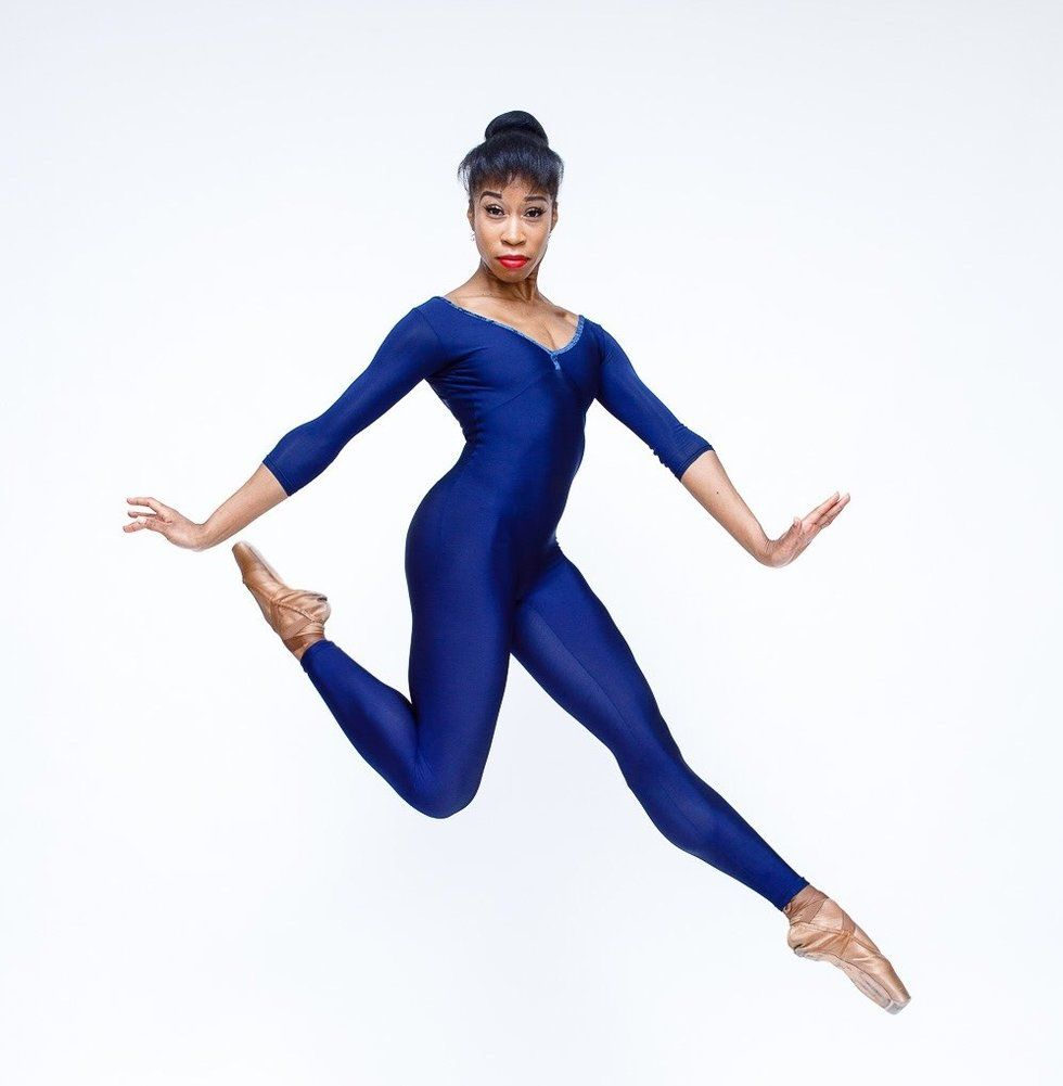 Lee is wearing a deep blue unitard and is leaping in a stag position, with flexed wrists, in front of a white background.