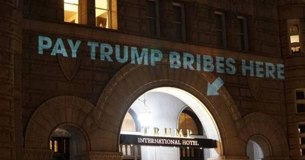 Artist Calls Out Trump's Conflicts Of Interest By Projecting Them Onto His Hotel
