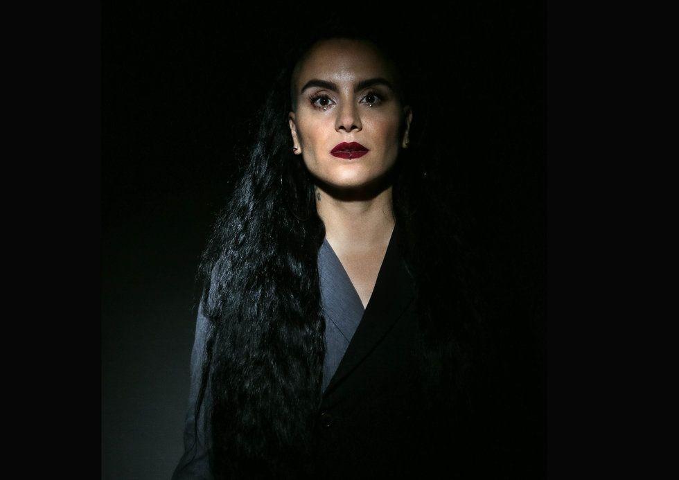 Sonya Tayeh stares into the camera, shining through the dark