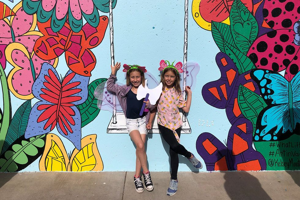 Two girls pose with Kelsey and Courtney's mural project in Vail