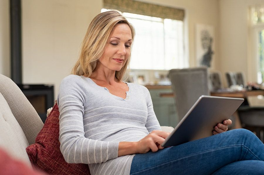 Professional woman uses tablet to read work email