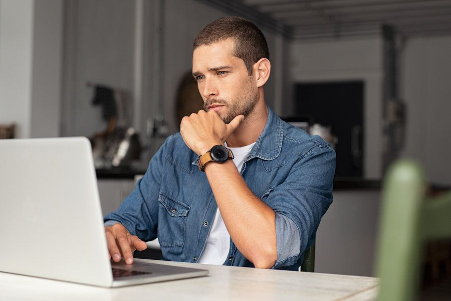 Man at computer thinking about whether or not to leave his job