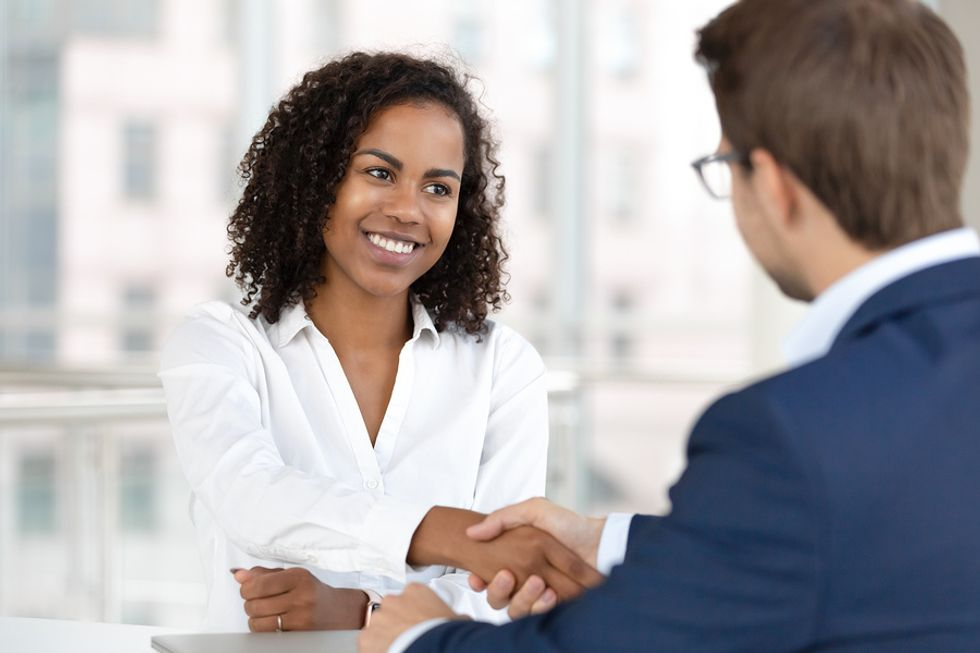 Woman shaking interviewer's hand during job interview