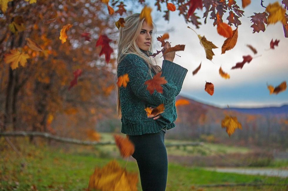 Woman posing candidly underneath a tree while autumn leaves fall midair