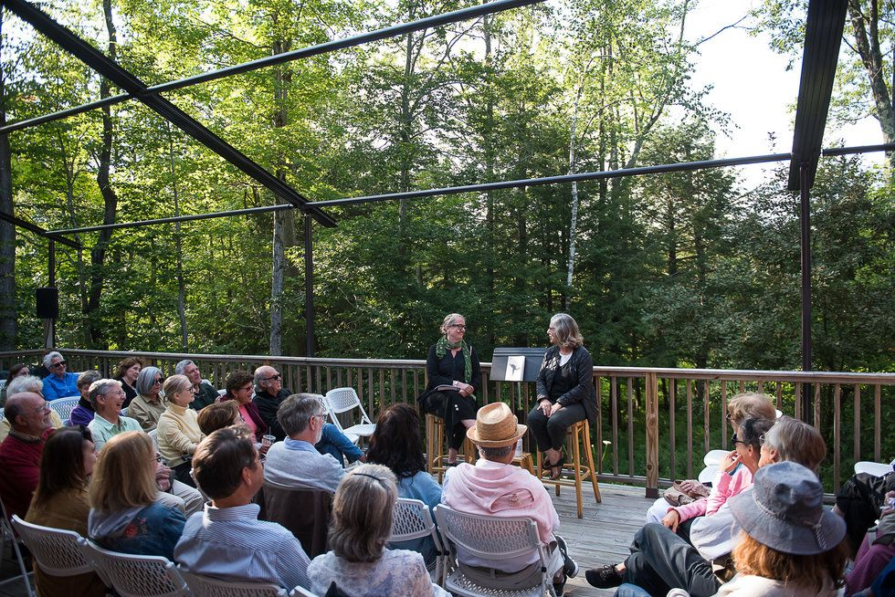 Two women sit on an outdoor porch, surrounded by trees. They are surrounded by people sitting around them.