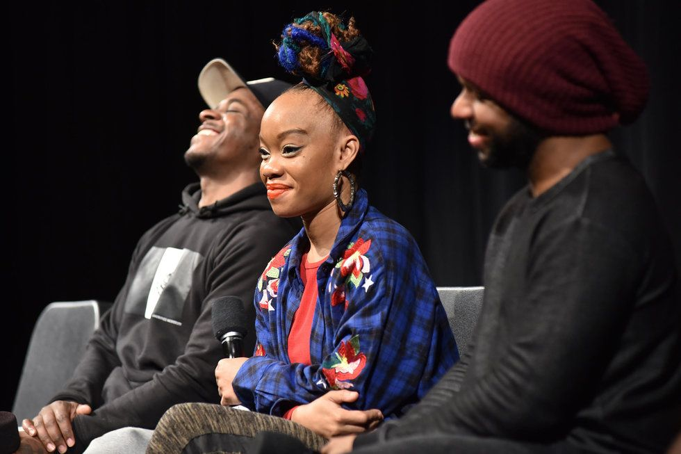 Camille A. Brown sits between two cast members. They are all laughing.