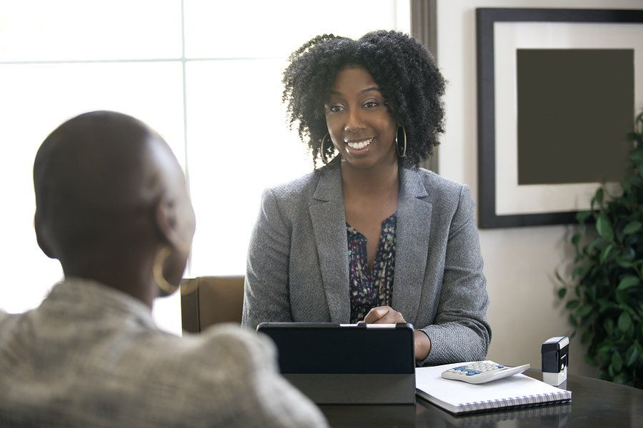 An accountant speaks with a client. Accountant is considered a recession proof career.