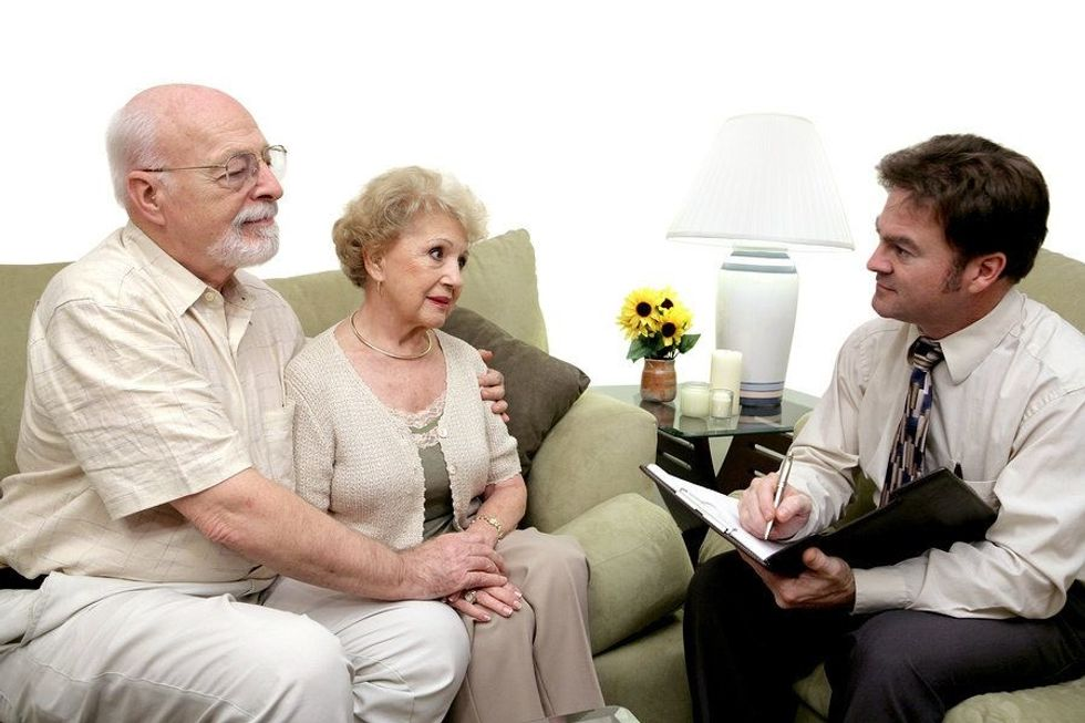 Funeral home director talks to a couple during a recession
