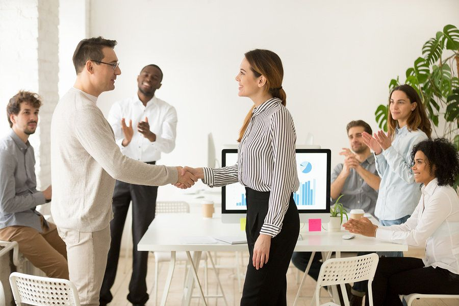 Manager congratulating a team member by shaking their hand at the office.