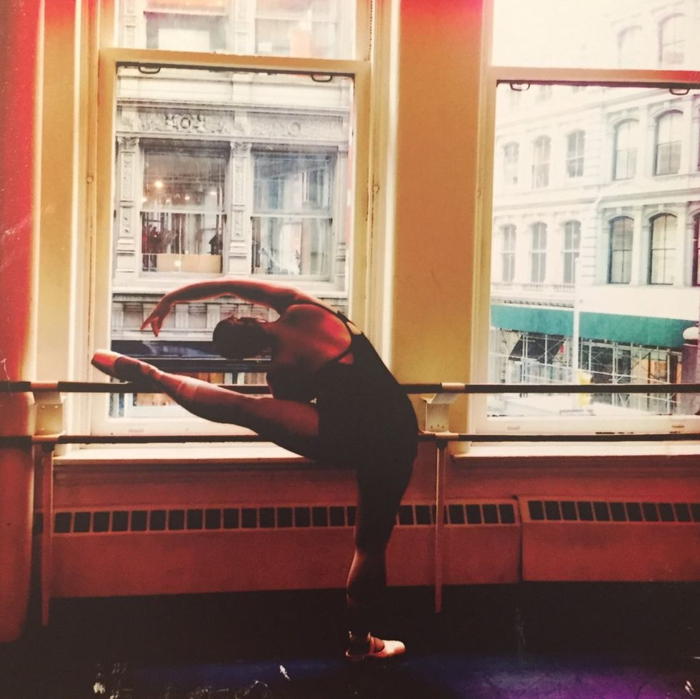Collier is facing the barre, with her left left resting atop it as she does a cambr\u00e9 to the left. She is wearing tights, pointe shoes and black leotard and has her hair in a bun. The barre is against two large windows, through which New York City buildings are visible.