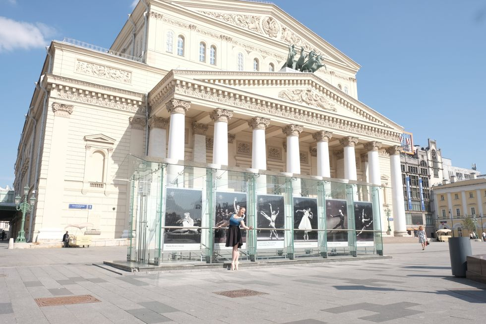 An open plaza in front of the grand Bolshoi Theatre. The sky is blue. Collier is standing at a barre in front of the theater, which features enlarged ballet photos set into glass.