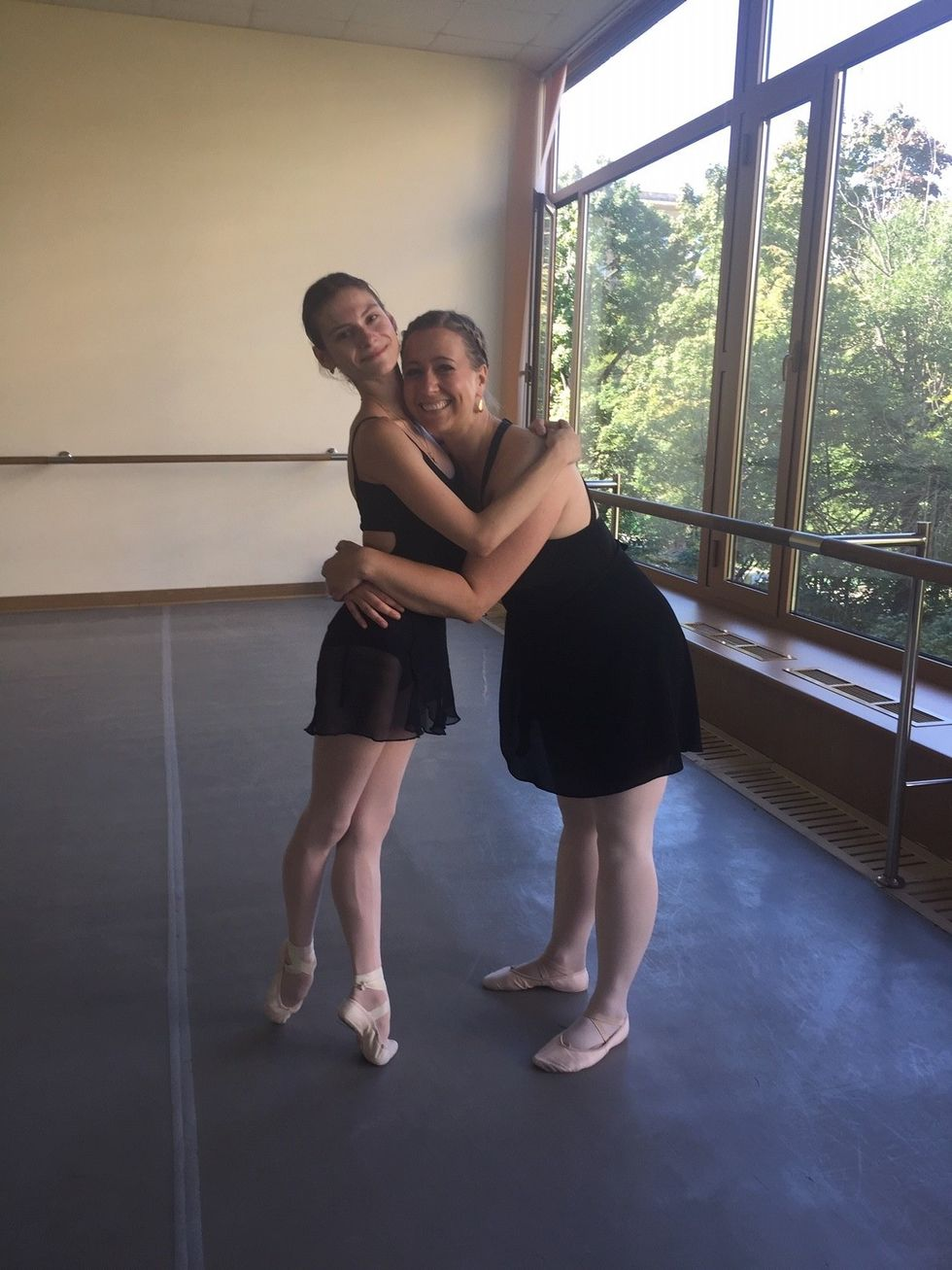 Strakhova (left) hugs Collier while Strakhova stands in relev\u00e9. Both women are wearing ballet slippers, pink tights, and black ballet skirts and leotards, while standing in a ballet studio.