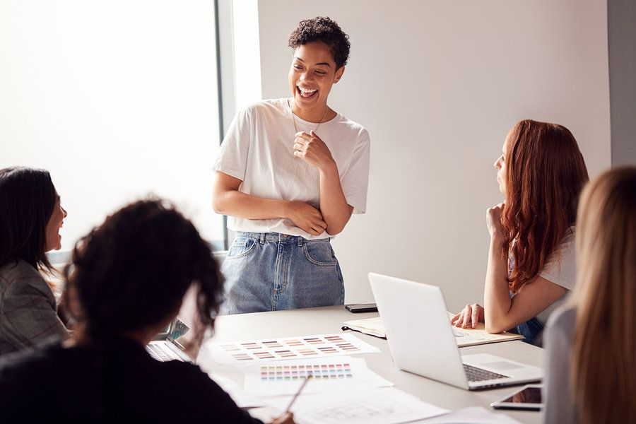 Female boss using her soft skills to effectively lead an office meeting.