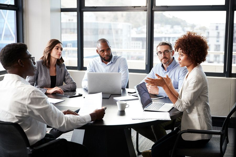 http://Woman sharpening her leadership skills by speaking up and sharing her opinion in an office meeting.