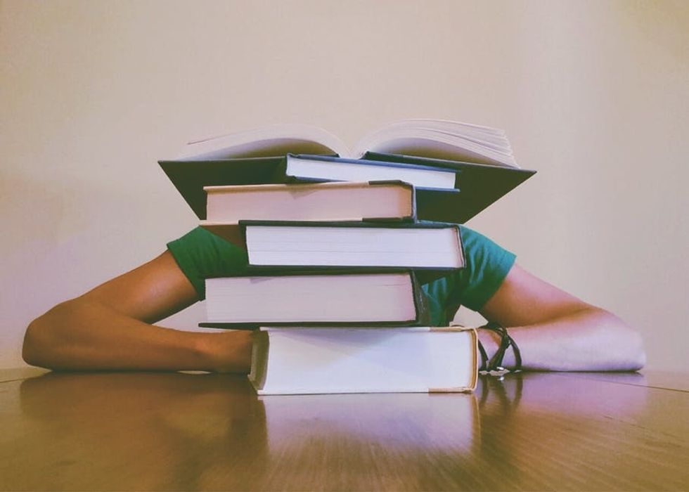 Person behind a large stack of books with their arms out to the side,..