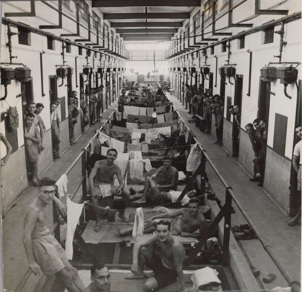 \u200bRecently liberated Allied soldiers in a prison corridor in Changi Prison, Singapore.