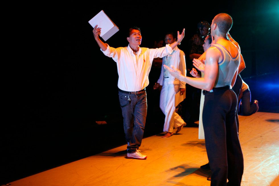 Masazumi Chaya in jeans and white button down, stands behind the curtain showing a movement to a dancer while giving notes