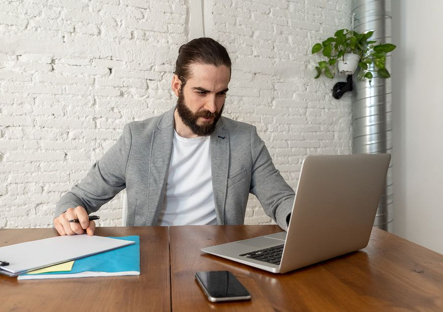 Man looking over his resume and formatting it to market his leadership skills.
