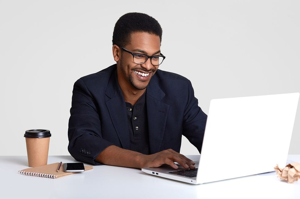 Smiling man working on his resume and tailoring it for a leadership job.