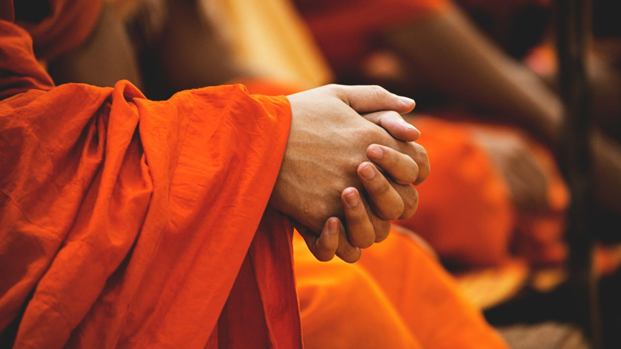 Buddhist monk clasps hands while reciting mantra.