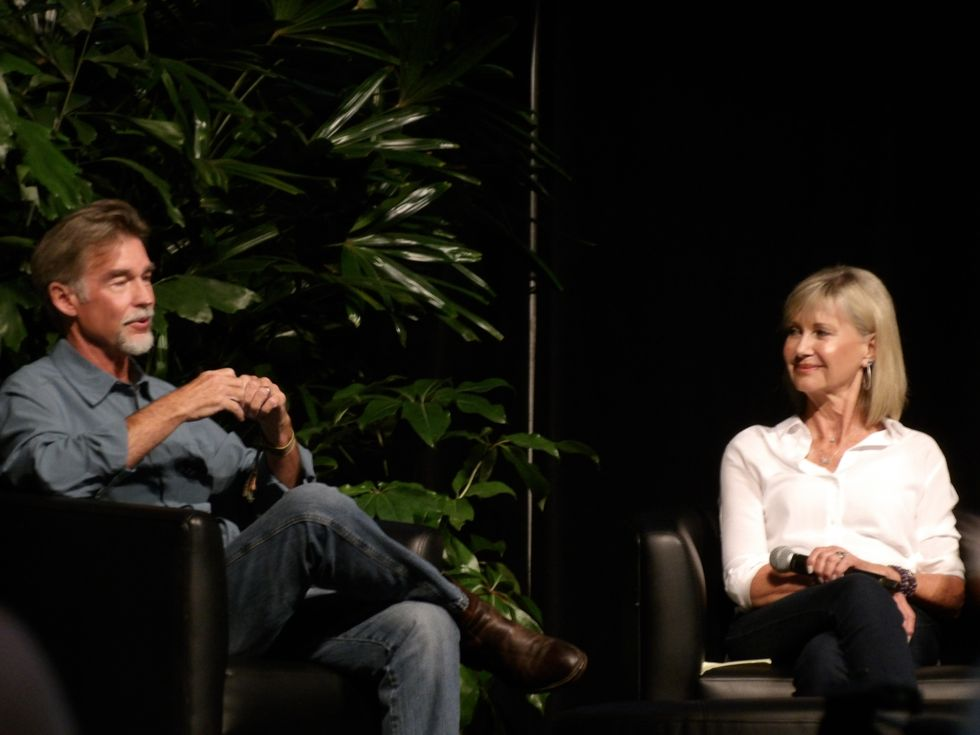 Amazon John Easterling and Olivia Newton-John sitting on black chairs with greenery in the background