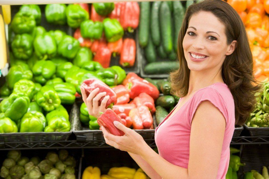 Woman picking out vegetables in order to eat them at work and feel happy in the workplace.